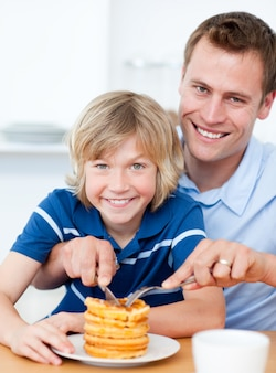 Smiling father and his son eating waffles