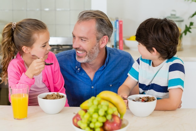 Smiling father and kids having breakfast in kitchen
