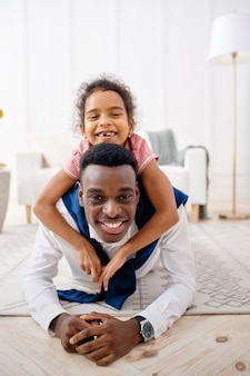 Smiling father and little daughter poses in living room. dad and female child leisures in their house together, good relationship