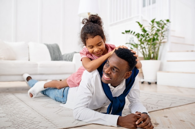 Smiling father and little daughter poses in living room. dad and female child leisures in their house together, happy relationship