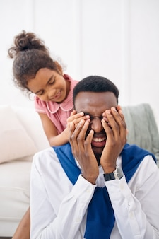 Smiling father and little daughter poses in living room