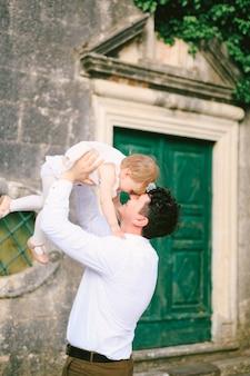 웃는 아버지는 오래된 문을 배경으로 어린 딸을 팔에 안고 키웠습니다.