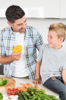 그의 아들 노란 고추를 보여주는 웃는 아버지