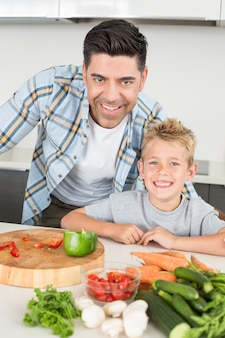 야채를 준비하는 방법 그의 아들을 보여주는 웃는 아버지