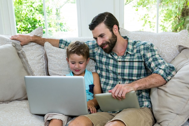 Smiling father sitting by son with laptop on sofa