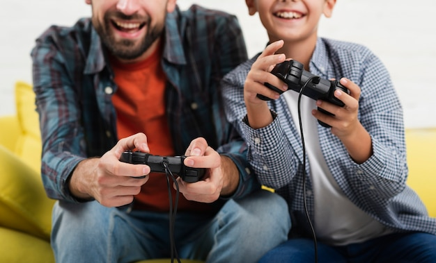 Smiling father and son playing on console