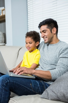 Smiling father and son using laptop on the sofa