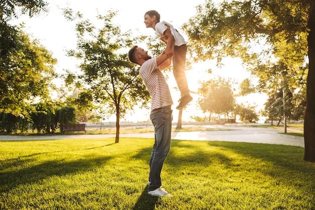 Улыбающийся отец проводит время со своим маленьким сыном в парке