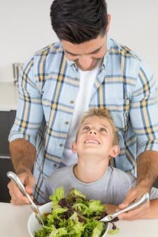 그의 작은 아들과 함께 아버지 던지기 샐러드 미소