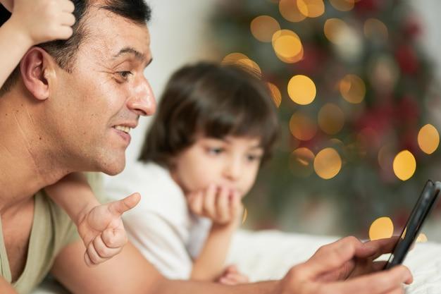 디지털 태블릿을 사용하는 웃고 있는 아버지는 귀여운 어린 아이들과 시간을 보내며 크리스마스 장식으로 꾸며진 집에서 침대에 누워 있습니다. 기술, 부모 개념