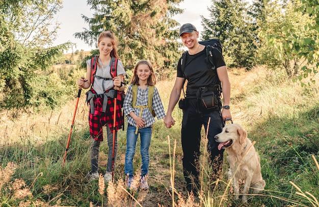 Улыбающийся отец с дочерьми и собакой в поход на солнечную гору