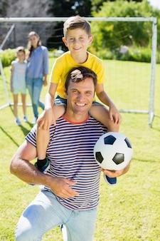 公園で息子を肩に乗せてサッカーで笑顔の父