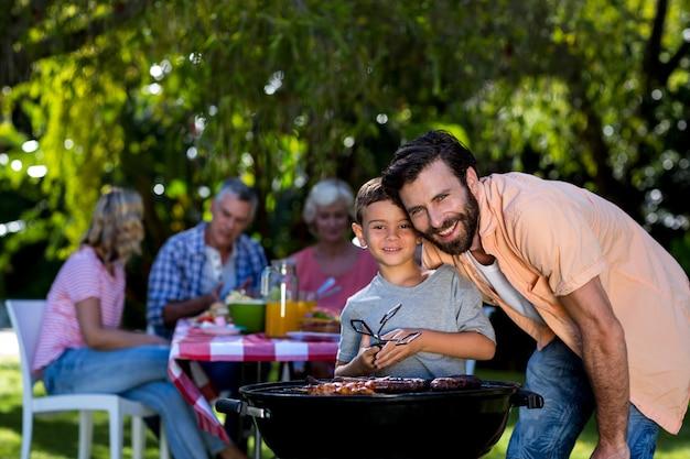 庭でバーベキューグリルで息子と笑顔の父