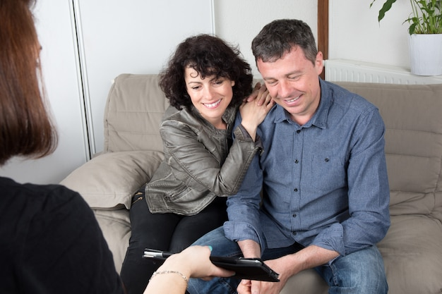Smiling female advisor showing house picture to couple on tablet