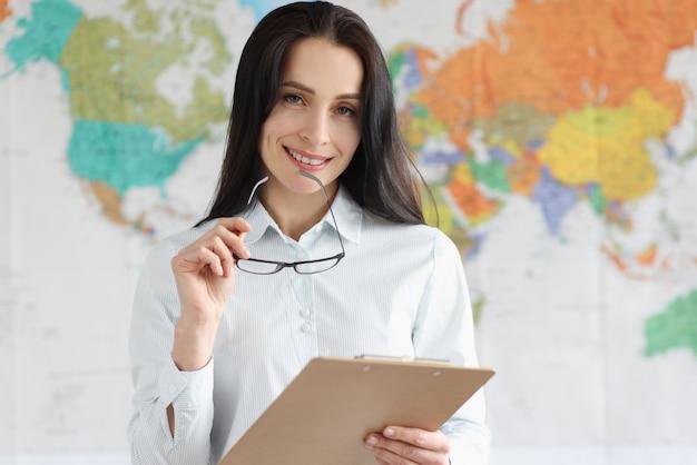 세계지도의 배경에 클립 보드를 들고 웃는 여성 에이전트