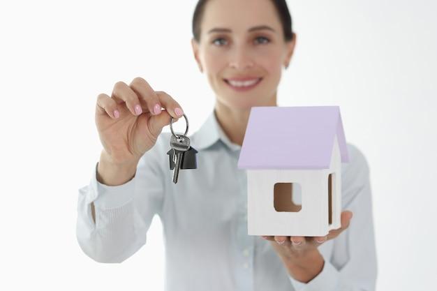 신용 토르 모기지 개념으로 작은 집과 열쇠를 들고 웃는 여성 에이전트