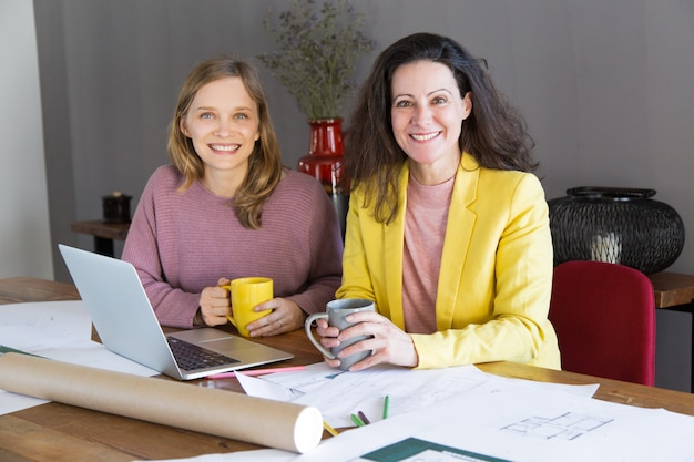 Smiling female architect and client having break