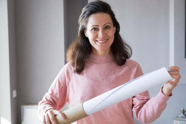 Smiling female architect pulling rolled-up drawing out of tube