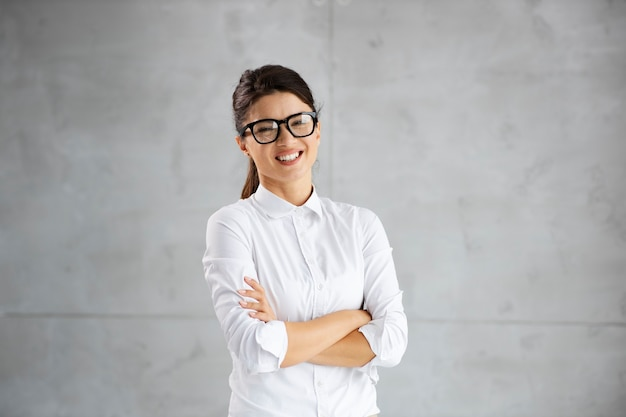 Smiling female architect standing with arms crossed.