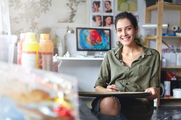 Sorridente artista femminile che indossa abiti casual seduto nel suo gabinetto con schizzi e vernice colorata, avendo espressione felice pur essendo felice di creare una bella immagine. pittore che lavora in officina