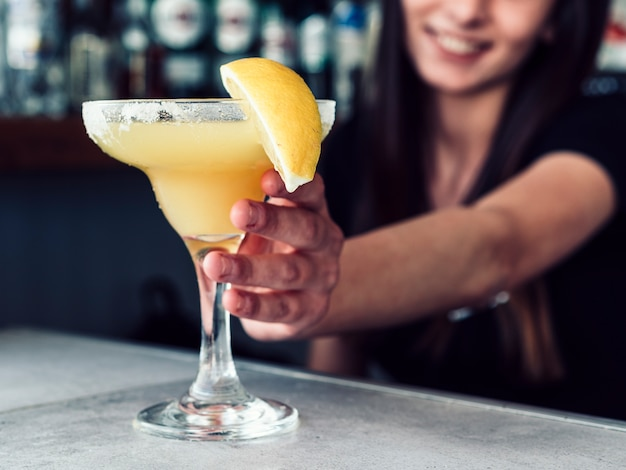 Smiling female bartender serving drink with lemon