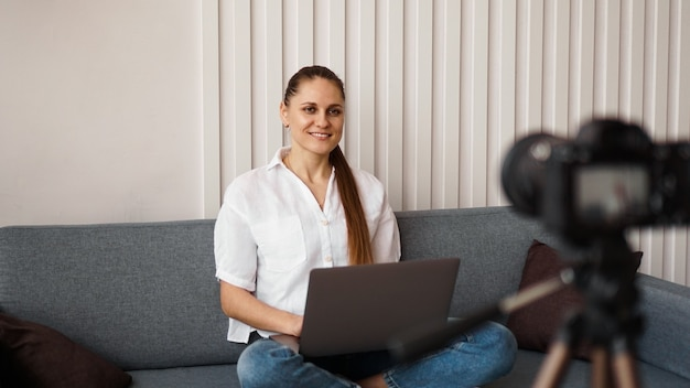 Smiling female blogger records a new video. she sits on the couch at home and holds a laptop. positive business blog concept.