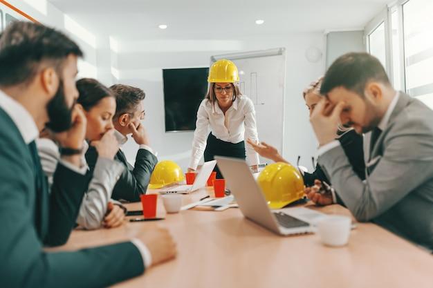 공식적인 마모와 책상에 기대어 프로젝트에 대해 이야기하는 머리에 보호용 헬멧으로 웃는 여성 보스. 건축가 비즈니스 개념. 힘든 시간은 지속되지 않고 힘든 시간은 지속됩니다.