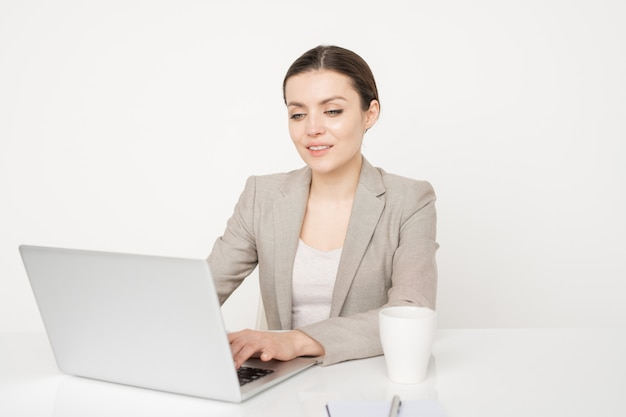 Smiling female broker in elegant suit looking at laptop display in front of her while surfing in the net for upgraded financial information