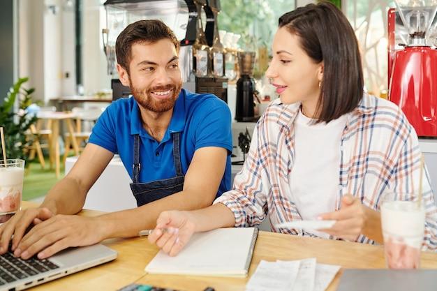 Улыбающаяся женщина-владелец кафе и бариста сидят за столом и планируют работу в следующем месяце