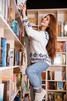 Smiling female college student taking book from shelf in library