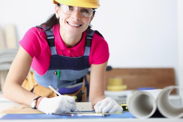 Улыбающаяся женщина-строитель в желтом шлеме склонилась над чертежами