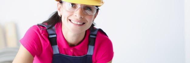 Smiling female construction worker in yellow helmet bent over blueprints