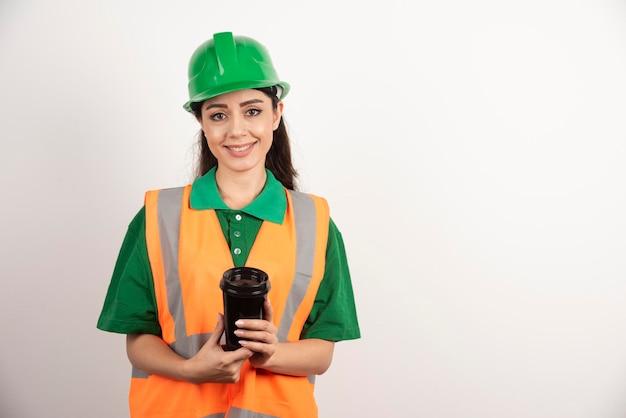 Costruttore femminile sorridente con la tazza nera. foto di alta qualità