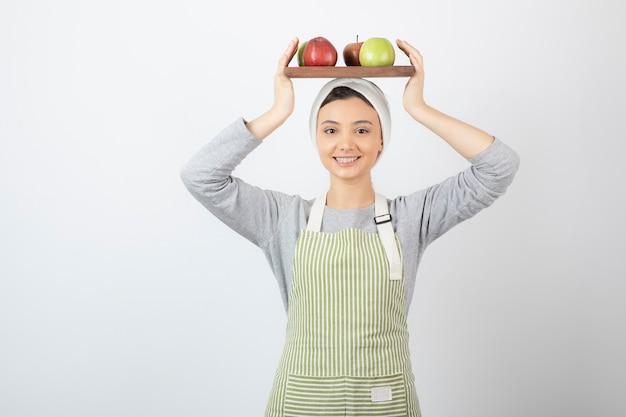 Улыбается женщина-повар, держа тарелку яблок на белом.