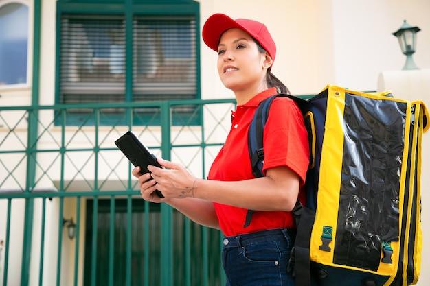 Corriere femminile sorridente con borsa termica gialla che consegna l'ordine a piedi. deliverywoman allegra in berretto rosso e camicia che camminano sulla strada con il tablet. servizio di consegna e concetto di acquisto online