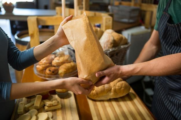 Улыбающаяся покупательница, получающая посылку от сотрудников пекарни на стойке