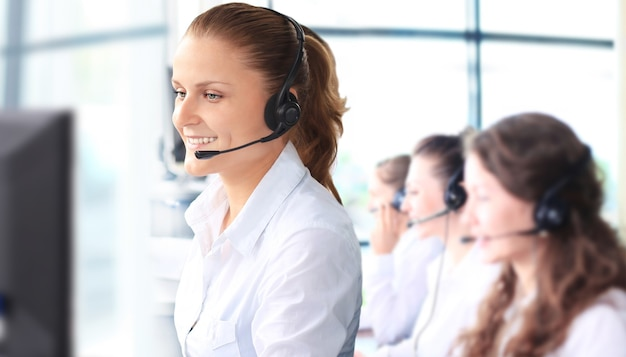 Улыбающийся женский представитель службы поддержки клиентов разговаривает по гарнитуре с коллегами в фоновом режиме в офисе
