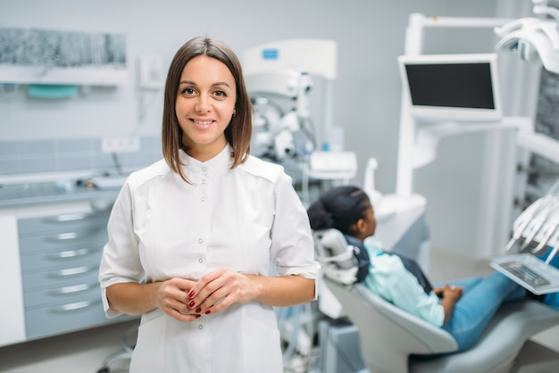 Smiling female dentist, dental clinic, patient in chair on background. woman in dentistry cabinet, stomatology, teeth care