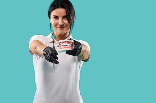 Улыбающаяся женщина-дантист держит гипсовую челюсть и стоматологическое зеркало и показывает их в камеру, позируя на синем фоне. сосредоточьтесь на руках.
