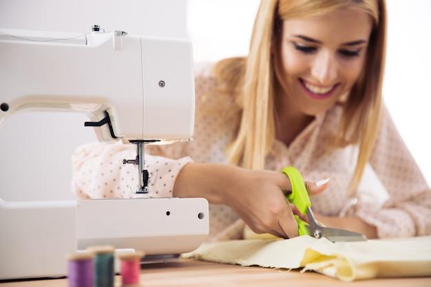 Улыбающаяся женщина-дизайнер режет ткань