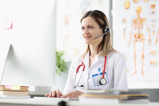 Улыбающаяся женщина-врач-консультант в наушниках оказывает медицинскую помощь удаленно