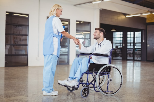 Smiling female doctor handshaking with doctor sitting on wheelchair