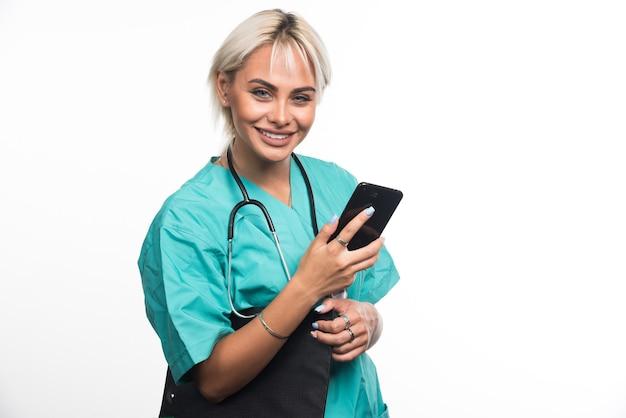 白い表面にクリップボードと電話を保持している女性医師の笑顔