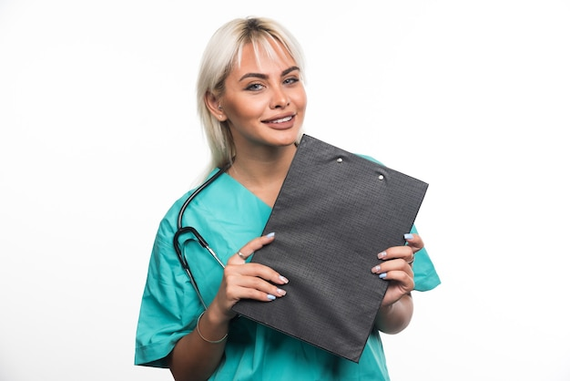 Medico femminile sorridente che tiene una lavagna per appunti sulla superficie bianca