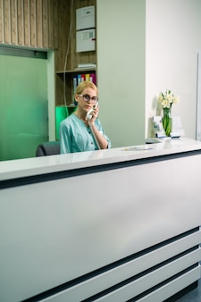 Smiling female doctor holding a receiver and answering phone calls, medical service. reception area.