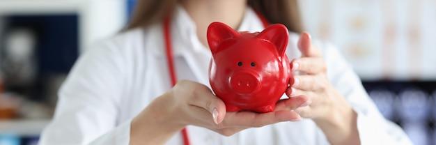 赤豚の貯金箱を保持している女性医師の笑顔