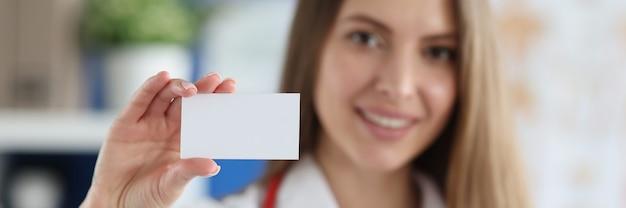 흰색 명함을 들고 웃는 여성 의사