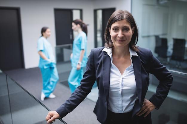 Улыбается женщина-врач в коридоре больницы
