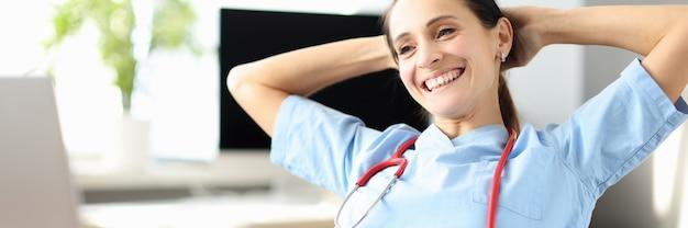 의료 사무실에서 웃는 여성 의사 테이블에 앉는 다.