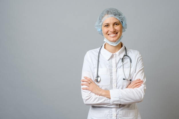 Smiling female doctor in lab coat with arms crossed